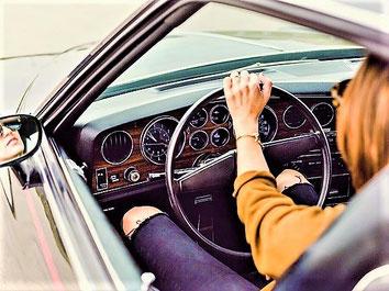 Eine Frau fährt Auto und sitzt am Steuer auf dem Weg in den Urlaub mit einer ERGO Jahres-Reiserücktritts-Versicherung