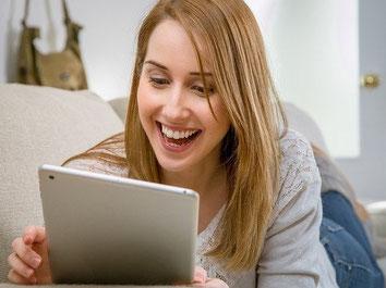 Frau bucht online eine Kurs-Versicherung/Seminar-Versicherung auf dem Tablet zur Absicherung ihres Privat-Kurs