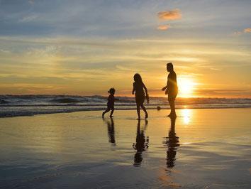 Familie im Sonnenuntergang an der Ostsee im Deutschland-Urlaub mit Reiserücktritts-Versicherung der ERGO