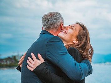 Ein Mann und eine Frau umarmen sich, sind glücklich über den Online-Abschluss einer ERGO Reisekosten-Rücktrittsversicherung gegen Hotel-Stornokosten