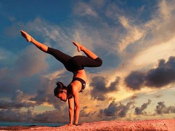 Eine Frau macht Yoga in der Abendsonne bei einem Yogakurs. Hoffentlich versichert mit einer Kurs-Versicherung.