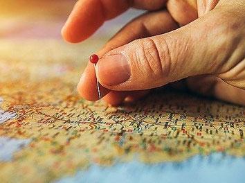 Ein Finger steckt eine Stecknadel in ein Bild mit Weltkarte als Zeichen für viele Reisen mit Jahres-Reiserücktritts-Versicherung der ERGO