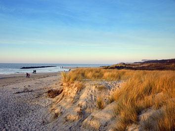 Urlaub in Deutschland: Ostseedünen mit einem fast leeren Strand und blauem Himmel