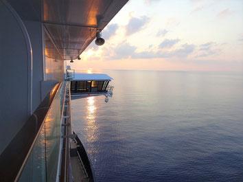 Blick vom Kreuzfahrtschiff aufs Meer in den Sonnenuntergang