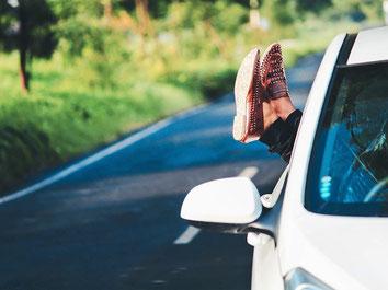 Füße aus dem Autofenster und ab in den Urlaub mit einer Reiserücktrittskostenversicherung der ERGO