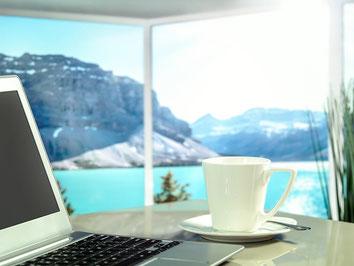 Kaffeetasse mit Laptop in einem Apartment mit Blick auf den See und die Berge bei einem Langzeit-Aufenthalt mit Reiserücktritts-Versicherung