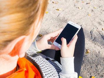 Frau bucht online eine Reiserücktritts-Versicherung mit dem Handy