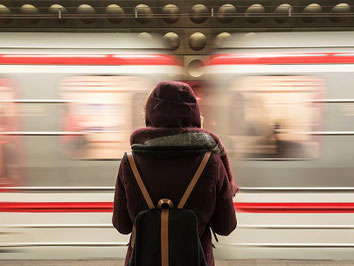 Frau steht vor einem fahrenden Zug und freut sich über ihre Reiseabsicherung