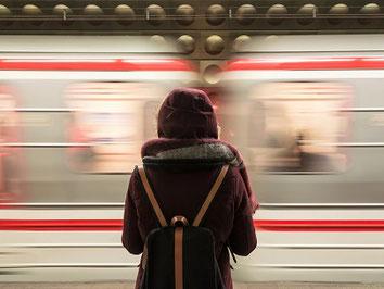 Frau steht vor einem fahrenden Zug und freut sich über ihre günstige Reiserücktritts-Versicherung für Bahnreisen