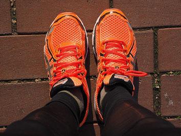 Orangene Laufschuhe sind gut, wenn man einen Sport-Kurs gebucht hat. Dafür gibt es extra die ERGO Stornokosten-Versicherung für Kurse und Seminare