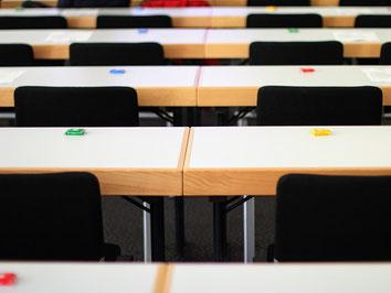 Leere Seminartische in einem Seminarraum. Schokolade wartet auf die Seminarteilnehmer.