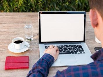 Junger Mann bucht online eine Reiserücktritts-Versicherung für Autoreisen mit dem Laptop