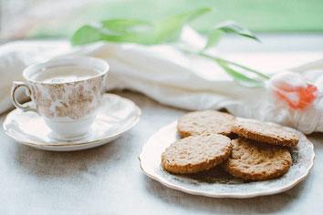 テーブルに置かれたマグカップとピンクのバラ、カスミソウ。
