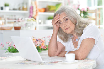Eine Frau sitzt mit dem Laptop am Tisch