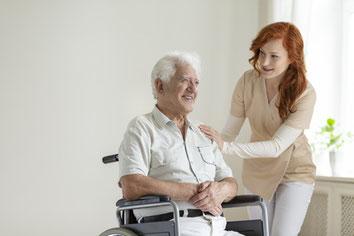 Ein Mann im Rollstuhl in Begleitung einer Helferin