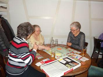 Drei Frauen spielen am Tisch Monopoly