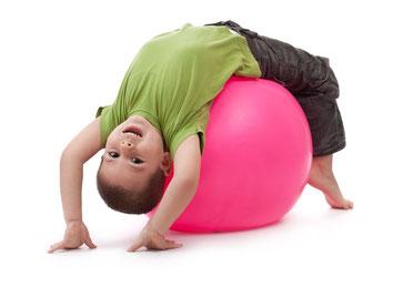 Hier sieht man einen kleinen Jungen beim Kinderturnen. Er klettert gerade auf allen Vieren über ein Hinderniss.