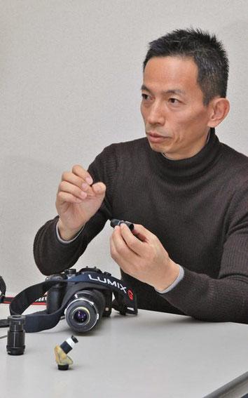動画撮影用虫の眼レンズ搭載カメラと鈴木 格氏。  虫の眼レンズを分解し、説明。
