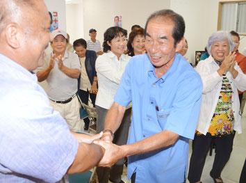 砂川県議と固い握手を交わす西大舛氏。支持者は万歳三唱して当選を祝った=29日、同選対事務所