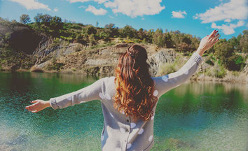 Woman standing with raised arms by lake to be happier
