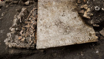 """Une pierre tombale a été retrouvée. Elle porte l'inscription """"Petrus Graper"""".© Denis Gliksman/Inrap"""