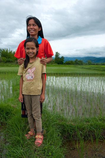 Mme Ta et sa fille dans la plaine de Kham. Depuis deux ans, elle cultive le riz selon après une formation SRS ce qui lui a permis d'augmenter ses rendements d'environ 30%