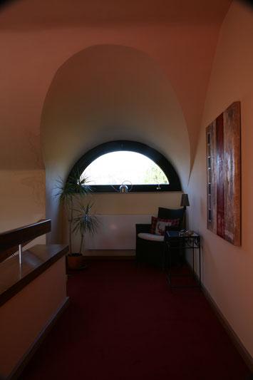 Immobilienfoto: Blick auf ein halbrundes Fenster, draußen ist es zu hell, drinnen zu dunkel