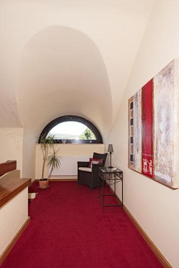 Immobilienfoto: Blick durch ein halbrundes Fenster, der Raum geblitzt, der Blick nach draußen überbelichtet