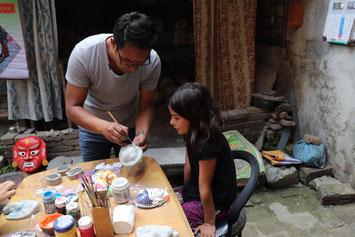 Mann hilft Kind beim bemalen der Maske