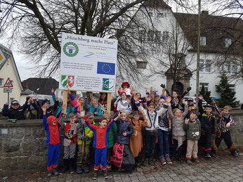 """Kostümierte Kinder vor dem Baustellenschild """"Hirschberg macht Platz"""""""