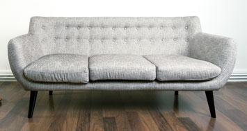 Graues, altes Sofa