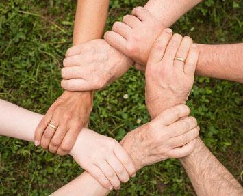 Sechs Hände, die sich im Kreis am Handgelenk fassen