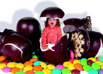 Kind inmitten von Riesensmarties und Riesenschaumküssen