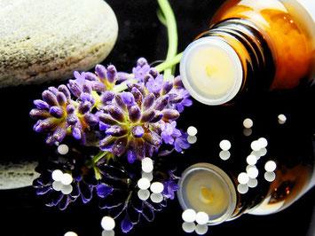 Medizinfhläschchen mit Globuli, davor Lavendel