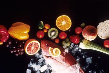 Un échantillon,  présenté sur un fond noir, d'aliments animaux (poisson) et végétaux frais (fruits et légumes)