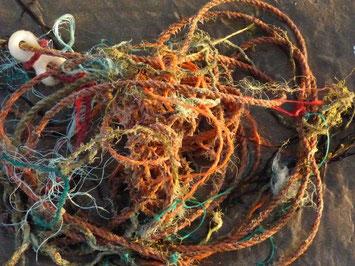bunte Seile und Stricke, verknäult am Strand