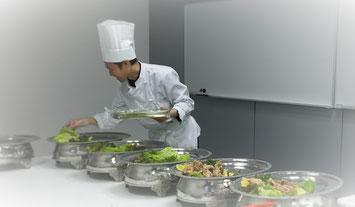葵庵のシェフがクライアントの会議室で料理を盛り付けしている写真
