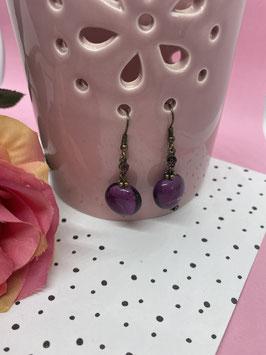 Een paar hangoorbellen met een paars glittersteentje en een paarse glassteen