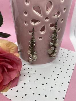 Een paar bronskleurige hangoorbellen met parels