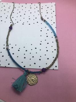Een goudkleurige ketting met turquoise kwast