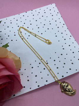 Een goudkleurige ketting met een hangertje van een Venetiaans masker