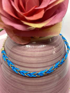 Een blauwe gevlochten enkelband