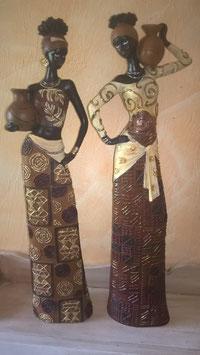 Afrikanische Frau (hier links im Bild: Topf auf dem Arm)