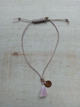 Cremefarbenes Textil-Armband mit rosa Troddel-Anhänger und goldfarbener Scheibe