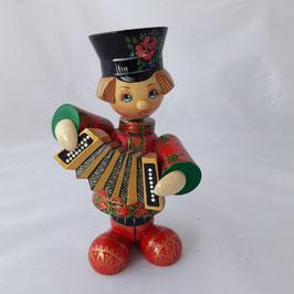 Holzpuppe Ivan mit einem Akkordeon in einem roten Hemd