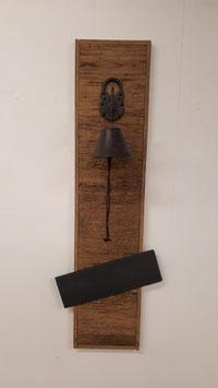 Altholzbrett mit Glocke und einem Schiefer.