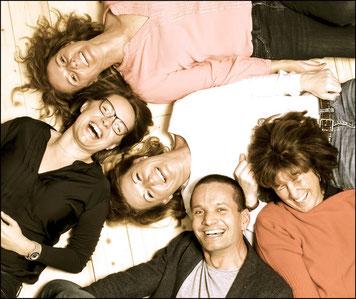 Der Arzt und seine Mitarbeiterinnen liegen lachend am Boden