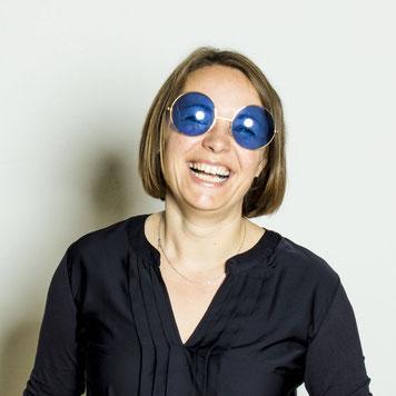 Maria lacht mit blauer Brille