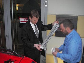 Verkaufsleiter Herr Steinhauer lässt es sich nicht nehmen, das Auto persönlich zu bekleben