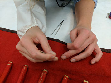 Hands of a European trained museum conservator working on stabilizing a fabric, after negotiations with the knowledge holder of the source community concluded that the treatment was necessary to honor the object. © Diana Gabler, 2017.